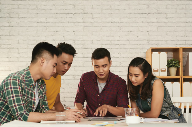 group-young-asian-men-woman-standing-together-around-table-looking-tablet_1098-18609